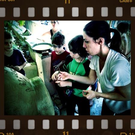 As crianças na escola construindo um forno de barro com pais e professora